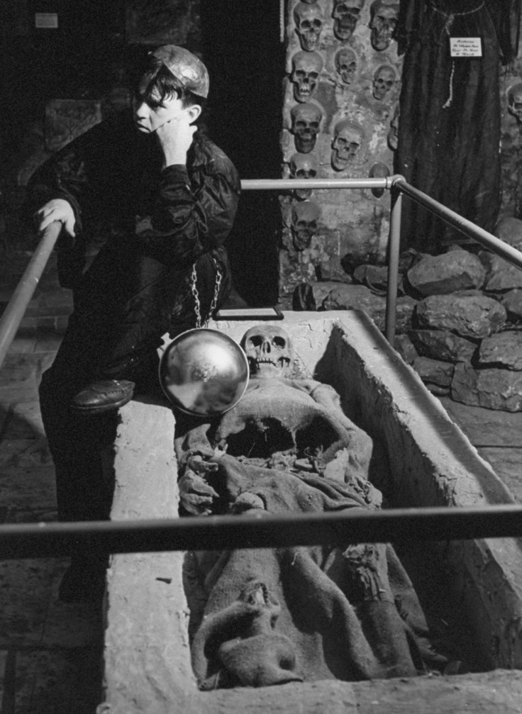 The keeper of the tombs sitting near a skeleton wrapped in burlap at the Catacombs Nightclub.  (Photo by Ralph Morse/Pix Inc./The LIFE Images Collection/Getty Images)