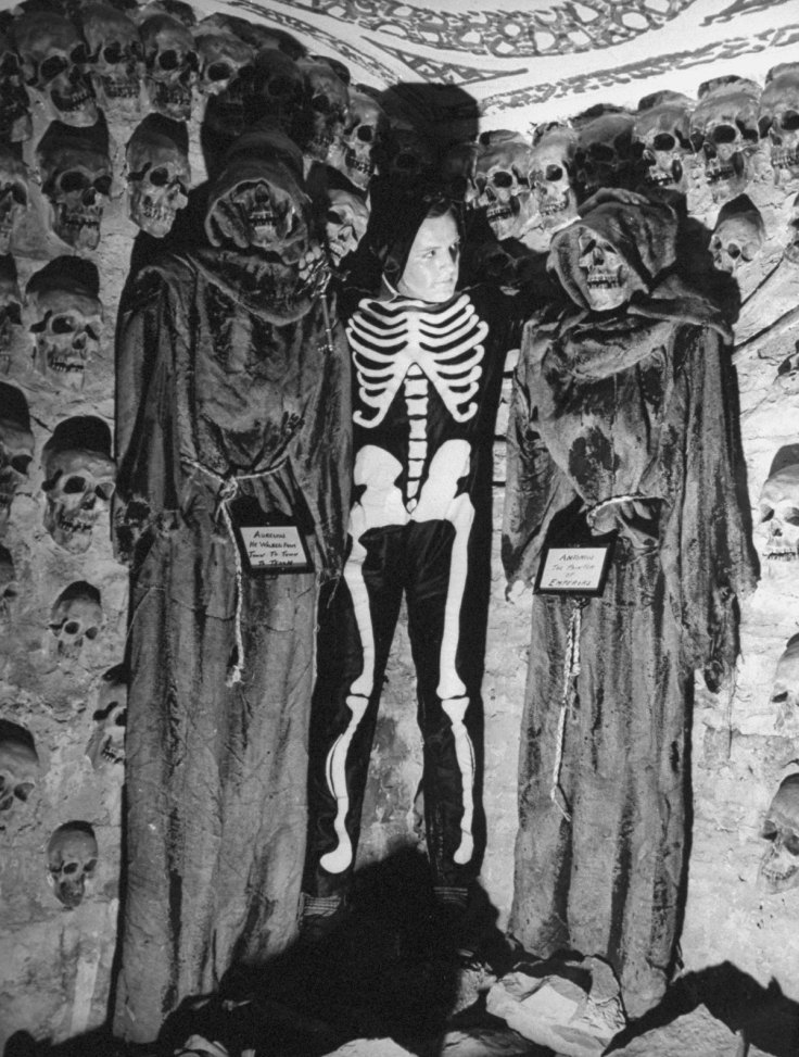 A young man, dressed as a skeleton, posing with plaster skulls and skeletons at the Catacombs Nightclub.  (Photo by Ralph Morse/Pix Inc./The LIFE Images Collection/Getty Images)