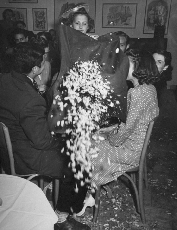 A woman throwing the crumbs from the tablecloth onto the floor at the Catacombs nightclub.  (Photo by Ralph Morse/Pix Inc./The LIFE Images Collection/Getty Images)