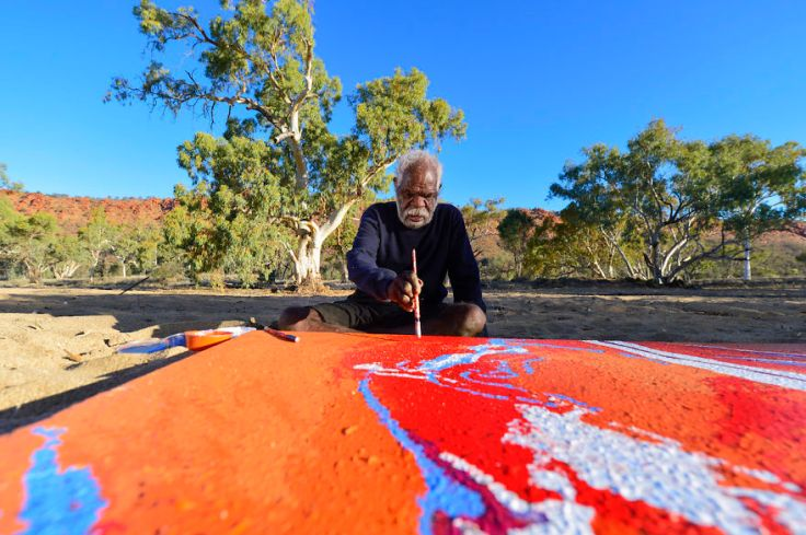 Yannima Tommy Watson paints in his country near Alice Springs